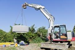 Excavator llifting concrete ring Royalty Free Stock Photography