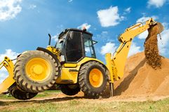 Excavator Loader with backhoe works. Wheel loader Excavator with backhoe unloading sand at eathmoving works in construction site Royalty Free Stock Images