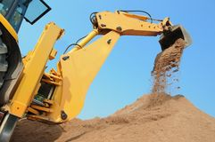 Excavator Loader with backhoe works. Wheel loader Excavator with backhoe unloading sand at eathmoving works in construction site Stock Photo