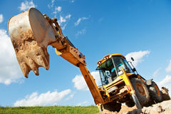 Excavator Loader with backhoe works. Wheel loader Excavator with backhoe unloading sand at eathmoving works in construction site Stock Photography