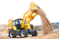 Excavator Loader with backhoe works. Wheel loader Excavator with backhoe unloading sand at eathmoving works in construction site Royalty Free Stock Photo