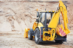 Excavator Loader with backhoe works. Wheel loader Excavator with backhoe loading sand at eathmoving works in construction site Stock Photos