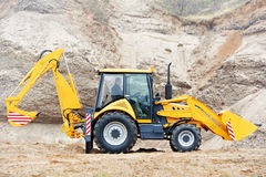 Excavator Loader with backhoe works. Wheel loader Excavator with backhoe loading sand at eathmoving works in construction site Stock Photo