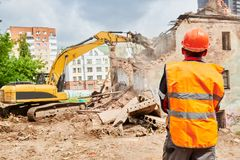 Excavator crasher machine at demolition on construction site. Excavator loader crushing machine at secondary demolition or destroying works on construction site royalty free stock photo