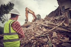 Excavator crasher machine at demolition on construction site. Excavator loader crushing machine at secondary demolition or destroying works on construction site stock photography