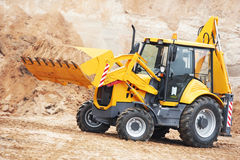 Excavator Loader at earth moving works. Wheel loader Excavator with backhoe unloading sand at eathmoving works in construction site quarry Royalty Free Stock Images