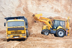 Excavator Loader at earth moving works. Wheel loader Excavator with backhoe loading sand into dumper truck at eathmoving works in construction site quarry Stock Image