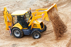 Excavator Loader at earth moving works. Wheel loader Excavator with backhoe unloading sand at eathmoving works in construction site quarry Stock Photography