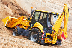 Excavator loader at earth moving works. Wheel loader excavator with backhoe unloading sand at eathmoving works in construction site quarry Royalty Free Stock Photography