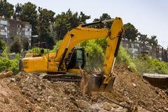 Yellow excavator machine with risen boom construction site. Excavator loader machine with risen boom construction site yellow excavator Stock Photo