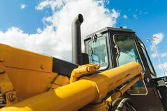Road-building machinery, tractors yellow excavators in open air in working position. Excavator Loader Machine. Side View of Front Hoe Loader. Industrial Vehicle Stock Photos
