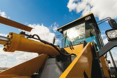 Road-building machinery, tractors yellow excavators in open air in working position. Excavator Loader Machine. Side View of Front Hoe Loader. Industrial Vehicle Royalty Free Stock Photography