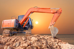Excavator loader machine with sunset background Stock Photos