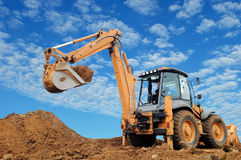 Excavator Loader with rised backhoe. Standing in sandpit with over cloudscape sky Stock Photography