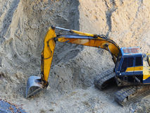 Excavator Loader with rised backhoe standing in sand Royalty Free Stock Photo