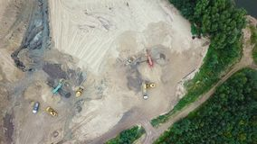 Excavator loader in sand quarry. View from above. Aerial view dumper trucks with cargo sand rides moving on territory sand factory. Tipper trucks on industrial stock video