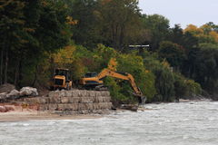 Excavator and Loader shore Up. Excavator and Loader working together to shore up the property with large rocks to protect from the lake's pounding waves and Royalty Free Stock Photography