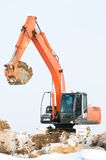 Excavator loader at winter works. Heavy excavator loader at winter frozen soil moving works in sandpit Stock Photo