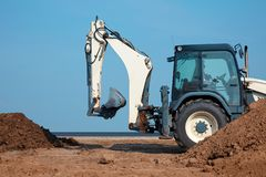 Excavator loader working at ground area on blue sky background, digging process. Bucket up. royalty free stock photography