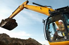 Excavator loader works. Excavator loader driver working at construction building area Royalty Free Stock Photos