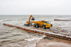 Excavator Loading A Truck Stones On The Beach Royalty Free Stock Image
