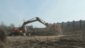 Excavator loading clay into the dump truck. On a construction site stock video