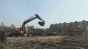 A excavator loading the clay into the dump truck. On a construction site stock video footage