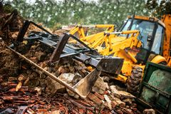 Excavator loading demolition debris and concrete wasted walls. In dumper trucks for recycling Royalty Free Stock Image