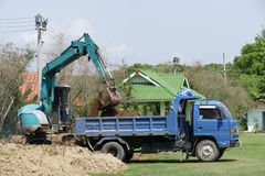 Excavator is loading dirt on truck Stock Photos