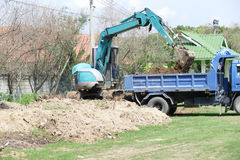 Excavator is loading dirt on truck Royalty Free Stock Photo