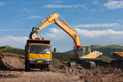 Excavator loading a dump truck. At a Country road Stock Image