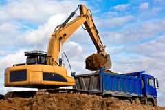 Excavator loading a dump truck Stock Photography