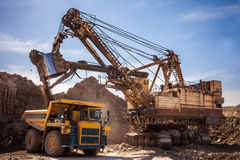 Excavator loading dump truck. At coal mining Royalty Free Stock Images