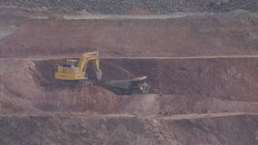 Excavator loading dump truck. Excavator in open pit mine loading a dump truck stock video