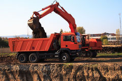 Excavator loading dumper truck Stock Photos