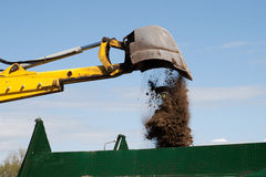 Excavator loading dumper truck. Excavator bucket with sand over blue sky Royalty Free Stock Image