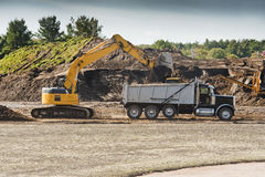 Excavator loading dumper truck Royalty Free Stock Photography