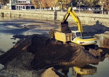 Excavator loading dumper truck. On a river royalty free stock images
