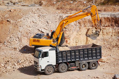 Excavator loading dumper truck with sand. At construction site Stock Photo