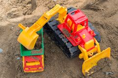 Excavator loading dumper truck with sand royalty free stock images