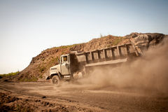 Excavator loading dumper truck with sand at a sand quarry Stock Photo