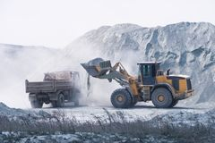 Excavator loading dumper truck with sand at a sand quarry Royalty Free Stock Photography