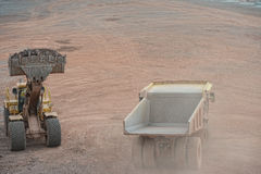 Excavator loading a dumper truck with stones Royalty Free Stock Photography