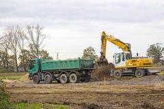 Excavator loading dumper truck tipper in sand pit Stock Images