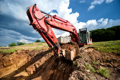 Excavator loading dumper truck tipper in sandpit Royalty Free Stock Photography