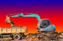 Excavator loading dumper truck tipper in sandpit Stock Images