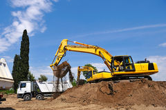 Excavator loading earth on truck Stock Photography