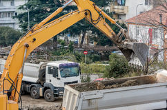 Excavator loading earth in the truck on construction site Stock Photo
