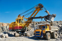 Excavator loading granite or ore into dump truck at opencast Stock Photos