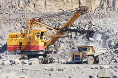 Excavator loading granite or ore into dump truck at opencast Royalty Free Stock Images